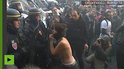 Une manifestante, torse nu, défie la police lors de la manifestation anti-Macron à Paris